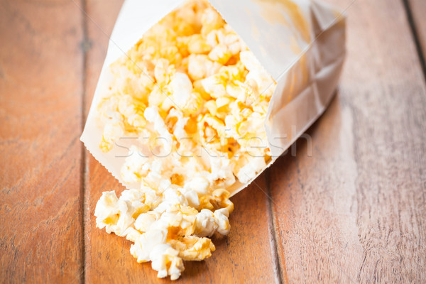 Popcorn paper bag opened with corn spilling out  Stock photo © nalinratphi