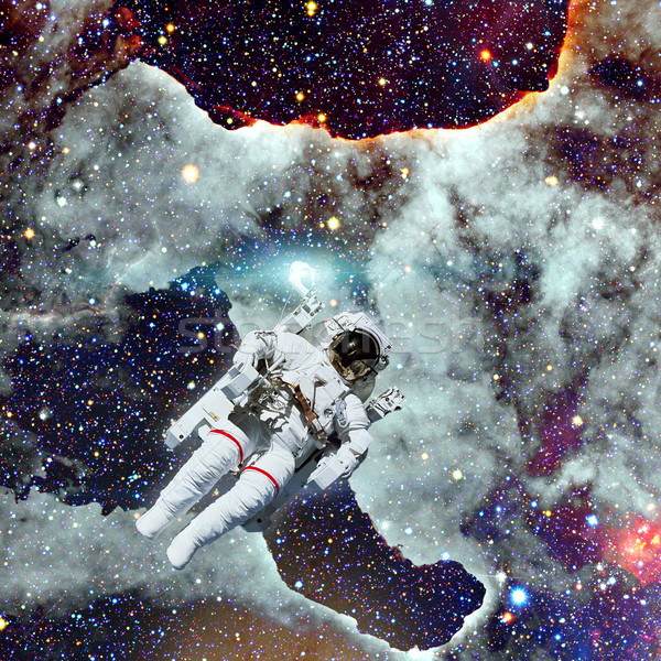 Stock photo: Astronaut in outer space. Nebula on the background.