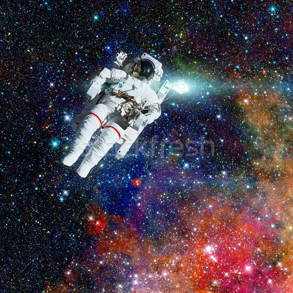 Stock photo: Astronaut in outer space. Nebula and stars on the background.