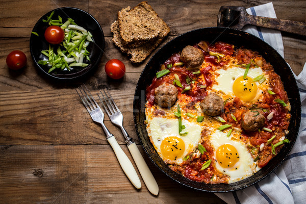 shakshuka, the Israeli dish of eggs, tomatoes and meatballs with herbs Stock photo © Natalya_Maiorova