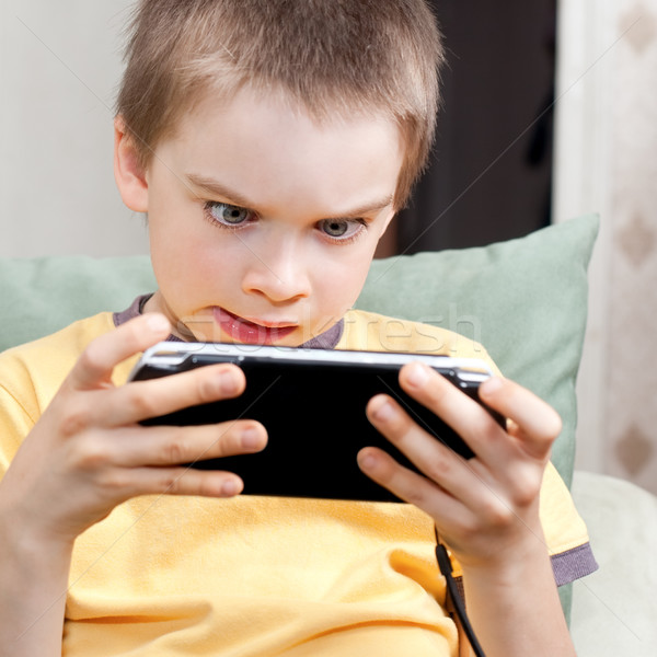Boy playing game console Stock photo © naumoid