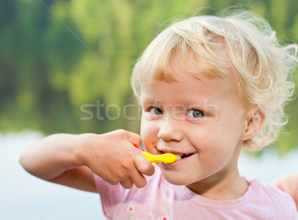 Blonde girl brushing teeth Stock photo © naumoid