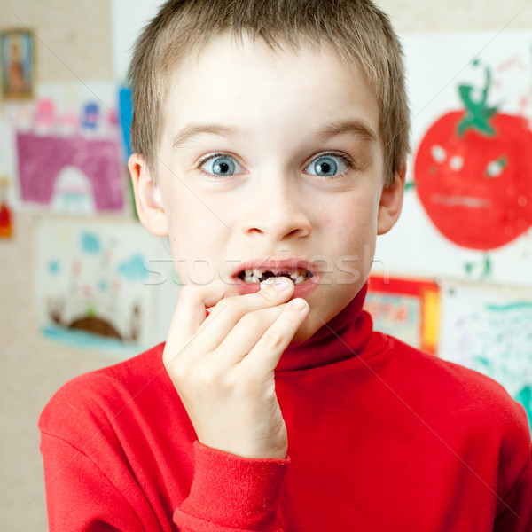 Boy holding missing teeth Stock photo © naumoid