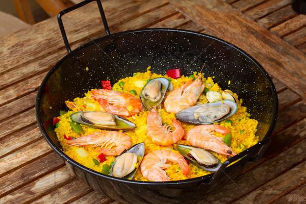 Paella in black pan Stock photo © neirfy