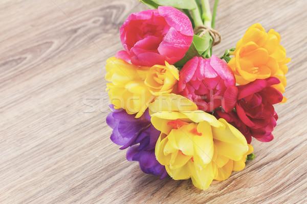 Tavaszi virágok fa asztal rózsaszín tulipánok citromsárga nárciszok Stock fotó © neirfy
