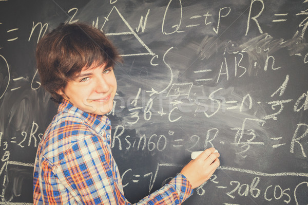 Boy writting on black board Stock photo © neirfy