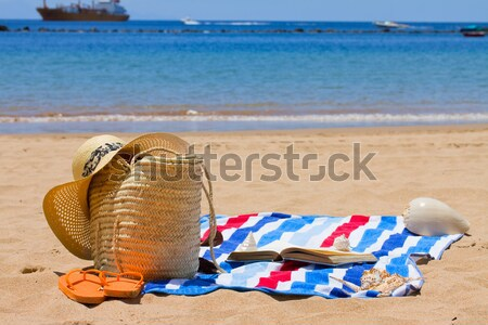 sunbathing accessories on sandy beach in straw bag Stock photo © neirfy