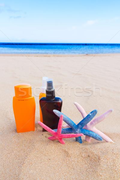 suntun creams on sandy beach Stock photo © neirfy