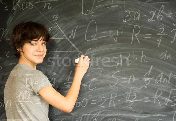 Boy writting on black board Stock photo © neirfy