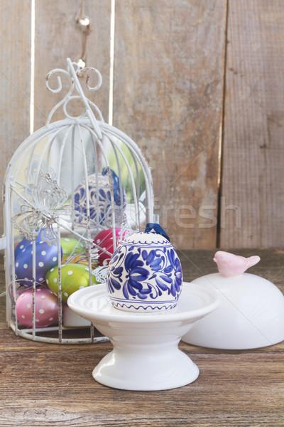 Húsvéti tojás húsvét színes tojás madárkalitka fa asztal természet Stock fotó © neirfy