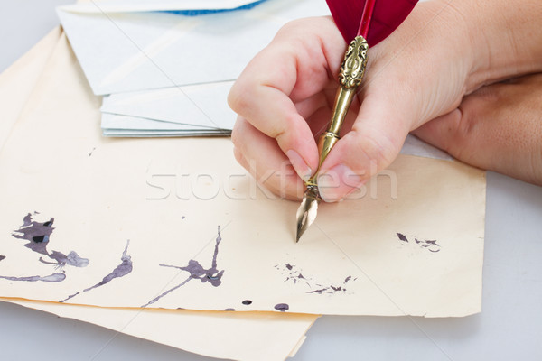 Stock photo: hand holding feather pen