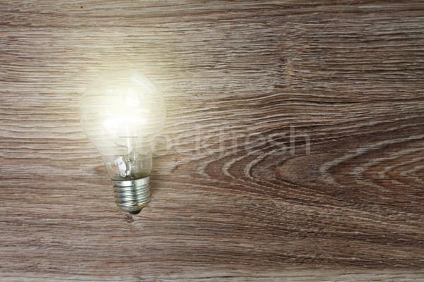 Illuminated light bulb on wood Stock photo © neirfy