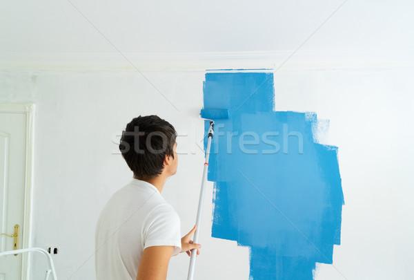 Csináld magad ház fiatalember festmény fal kék Stock fotó © neirfy