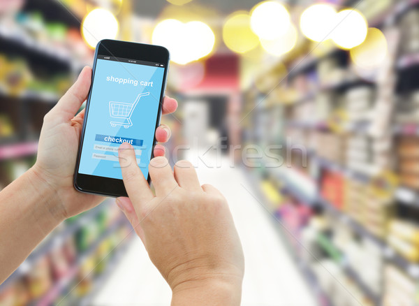 hand holding a modern smartphone in supermarket Stock photo © neirfy