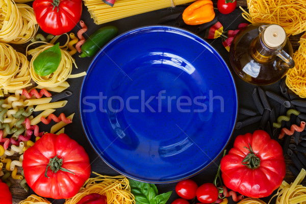 Raw pasta with ingridients and blue plate Stock photo © neirfy