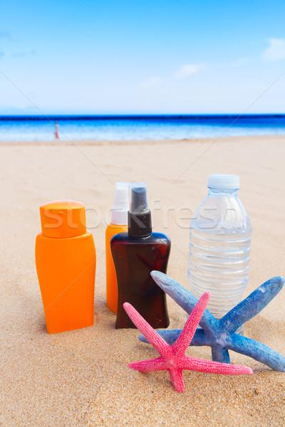 water with suntun creams on sandy beach Stock photo © neirfy