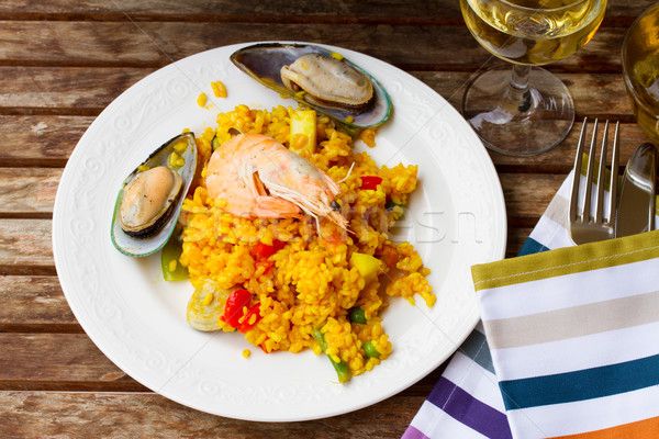 Paella served in white plate on wooden table Stock photo © neirfy