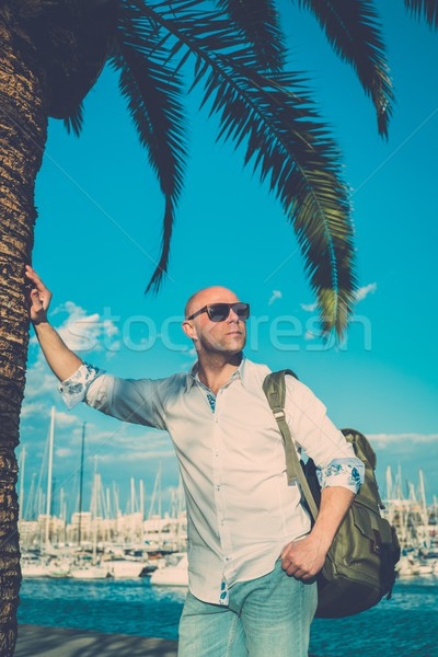Middle-aged man with backpack standing near palm tree against yacht port Stock photo © Nejron