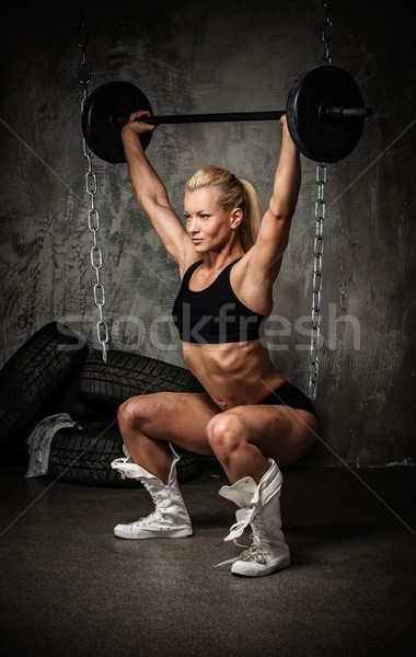 Beautiful muscular bodybuilder woman doing exercise with weights Stock photo © Nejron