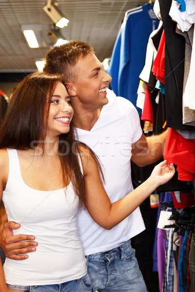 Beautiful young couple choosing sportswear in sport outlet Stock photo © Nejron