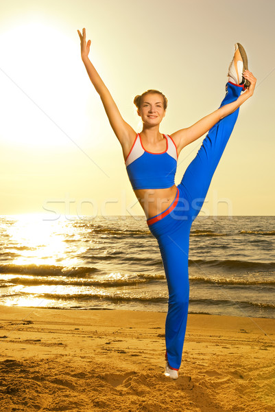 Beautiful young woman doing fitness exercise on a beach at sunse Stock photo © Nejron