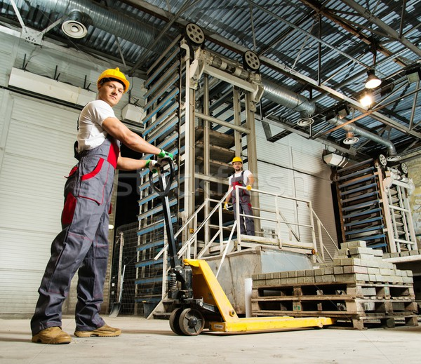 Young worker moving paving stones with pallet truck on a factory Stock photo © Nejron