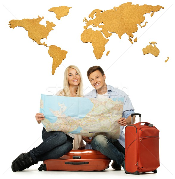 Smiling beautiful young couple with a map sitting on a suitcase Stock photo © Nejron