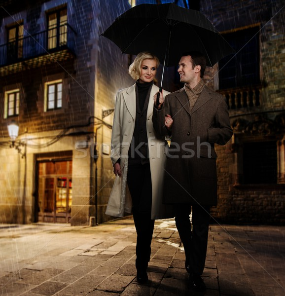 Elegant couple in autumnal coats walking in the rain outdoors at night Stock photo © Nejron