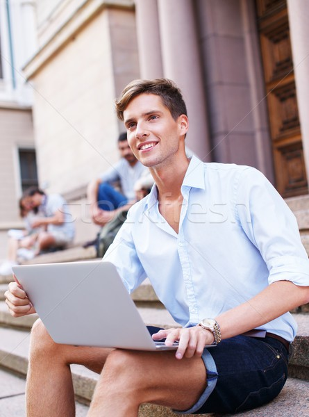 Stock photo: Handsome young man with laptop sitting on a steps outdoors