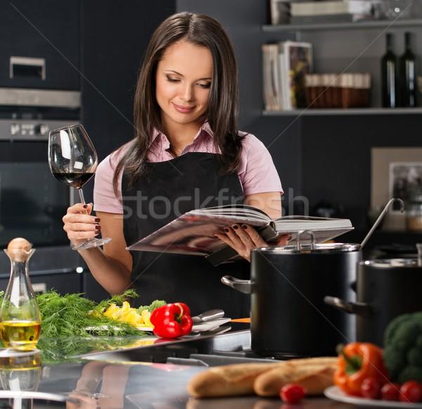 Wesoły młoda kobieta fartuch nowoczesne kuchnia książka kucharska Zdjęcia stock © Nejron