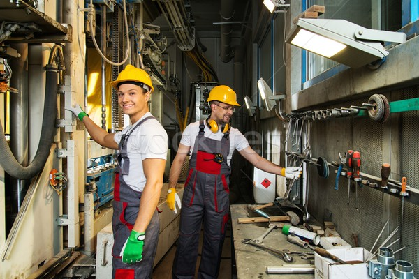 Stock photo: Two worker in a safety hats  on a factory near near machine