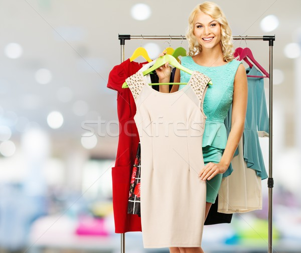 Smiling blond woman choosing clothes on a rack in a shopping mall   Stock photo © Nejron