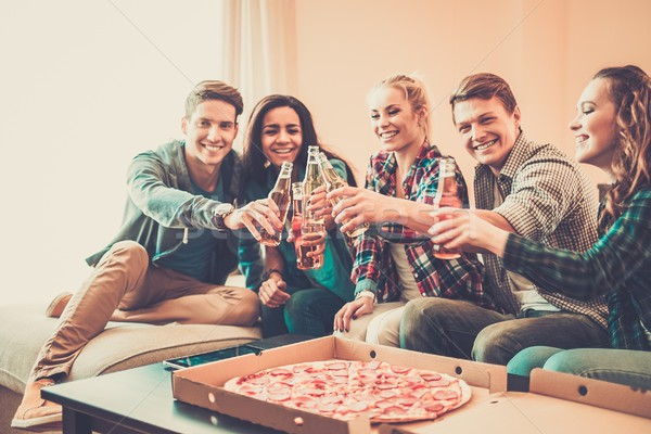 Multi-ethnic friends with pizza and bottles of drinks having party Stock photo © Nejron