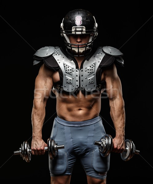 American football player with dumbbells wearing helmet and protective armour  Stock photo © Nejron