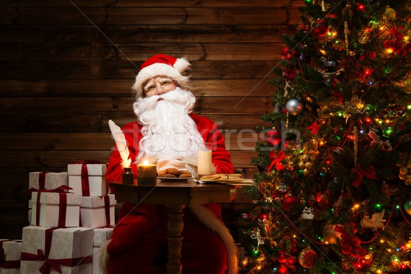 Santa Claus in wooden home interior sitting behind table with milk and oatmeal cookies Stock photo © Nejron