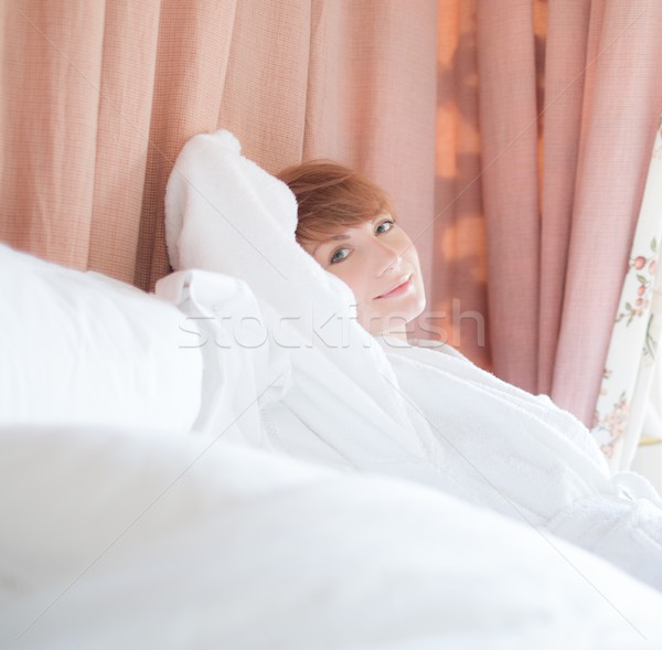 Beautiful woman in bathrobe with a short haircut lying on a  bed Stock photo © Nejron