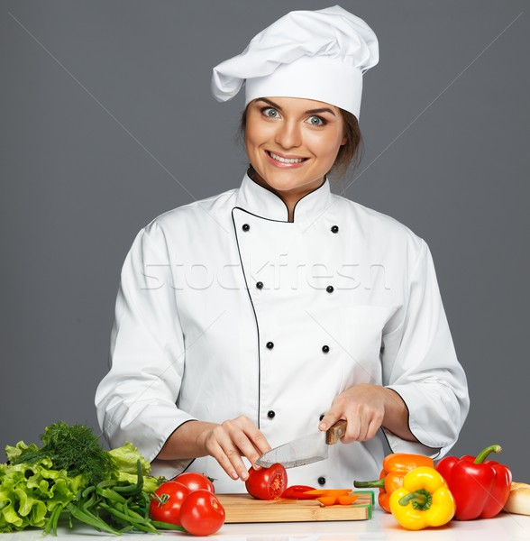 Funny mad young woman cook cutting fresh tomatoes Stock photo © Nejron