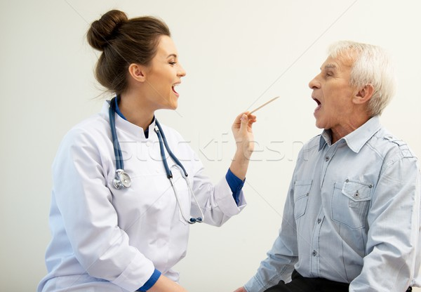 Senior man at doctors's office appointment checking throat  Stock photo © Nejron