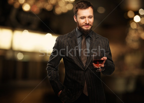 Handsome well-dressed man in jacket with glass of beverage  Stock photo © Nejron