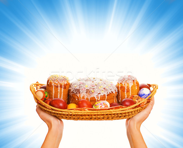 Hands holding woven basket full with easter eggs and easter cake Stock photo © Nejron