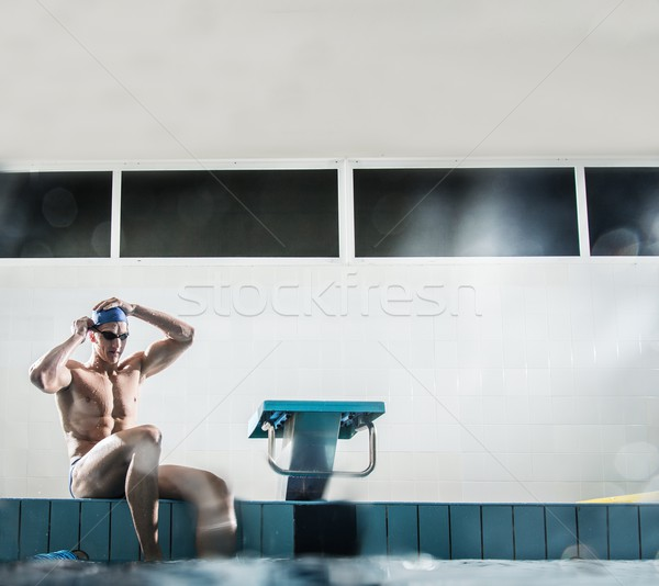 Young muscular swimmer putting on swimming goggles Stock photo © Nejron
