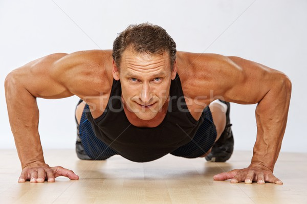 Handsome muscular man doing push-up. Stock photo © Nejron