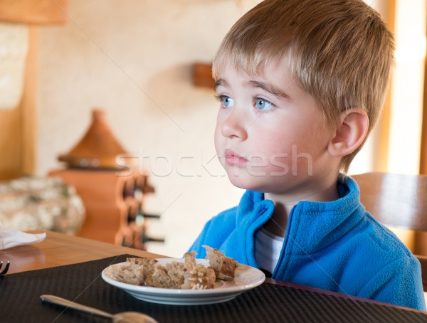 Grievous little boy sitting behind table with full plate Stock photo © Nejron