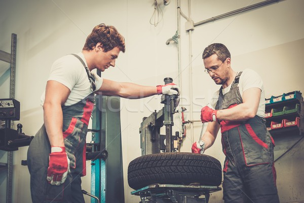 Two mechanics changing tire on a wheel in a car workshop Stock photo © Nejron