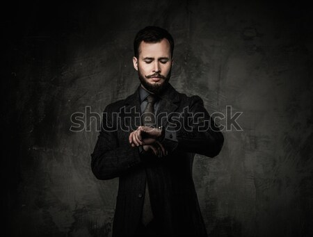 Handsome well-dressed man in jacket looking at wrist watch  Stock photo © Nejron