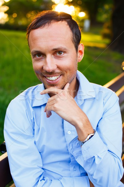 Happy handsome middle-aged man sitting on a bench outdoors  Stock photo © Nejron