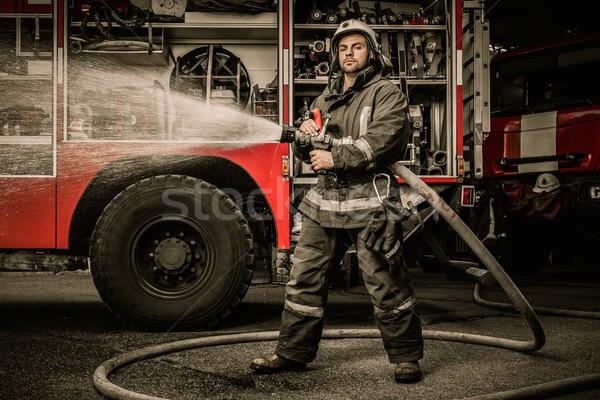 Stockfoto: Brandweerman · water · vrachtwagen · uitrusting · gebouw