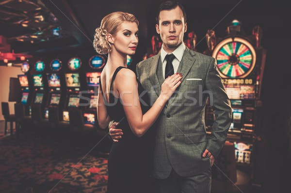 Well-dressed couple against slot machines Stock photo © Nejron