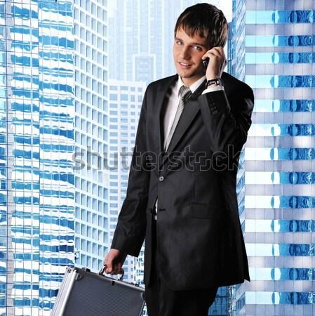 Happy businessman against his office building Stock photo © Nejron