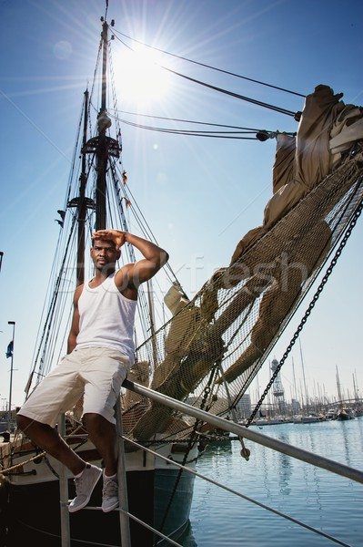 Handsome afro-american man against boat in port. Stock photo © Nejron